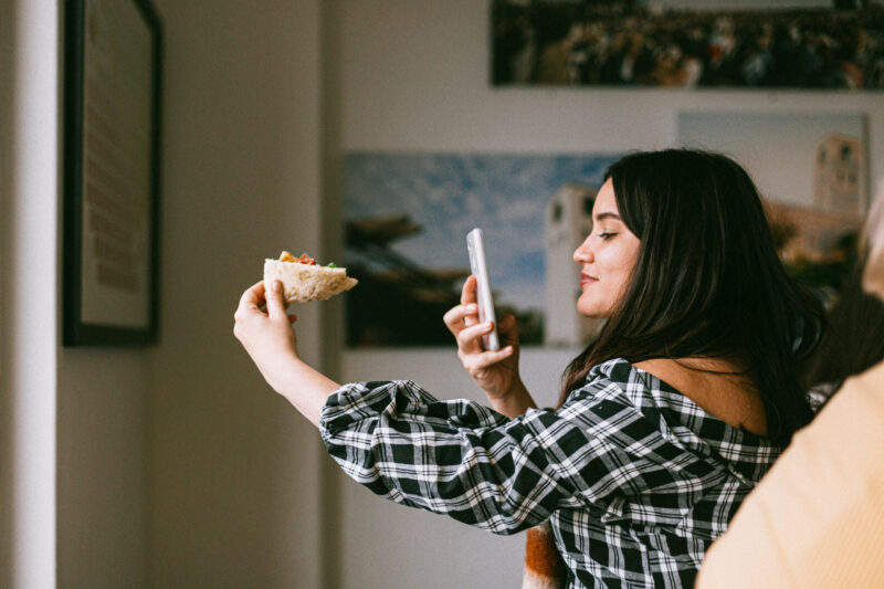 Influencers taking a photo of food with her phone