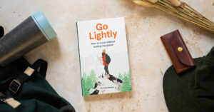 """A book is centred in a flatlay with the title Go Lightly written in orange text. The sub-heading says """"How to travel without hurting the planet."""" The book is authored by Nina Karnikowski."""