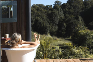 Women in an outdoor tub on a timber deck, overlooking the green mountain trees. Sustainable travel with Nina Karnikowski.