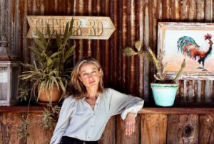 Portrait of Nina Karnikowski, sustainable traveller, resting her arm on a bench and smiling at the camera.