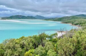 Landscape view of the Whitsunday Islands on a cloudy day. Blue waters surrounded by lush green mountains.